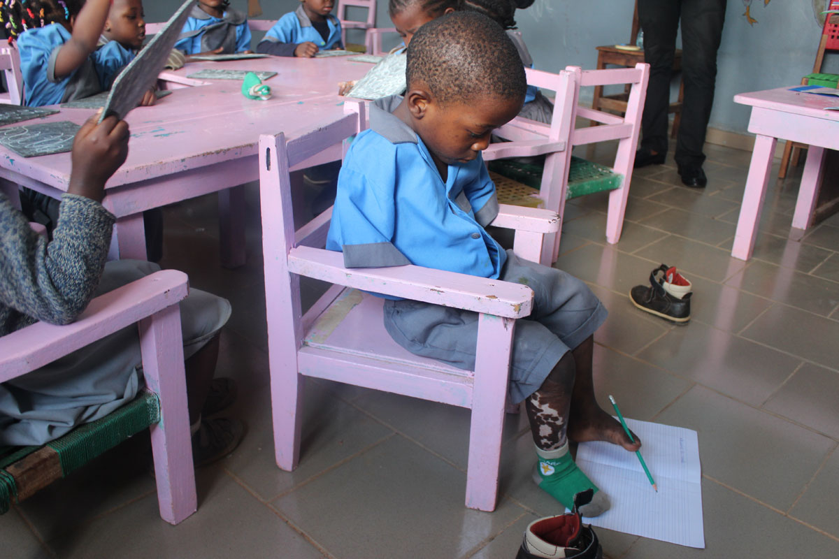 Adaptation Training a child without hands to use legs to write